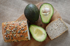Avocado and a loaf of pumpkin-bread. Loaf of bread with cut avocados Royalty Free Stock Photos