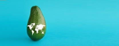 Avocado maturo verde con una mappa di mondo per illustrare uno stile di vita sano, bio- ristorante di nutrizione di dieta vegetar fotografia stock