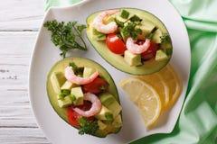 Avocado met garnalensalade en groentenclose-up die wordt gevuld horizontaal Stock Fotografie