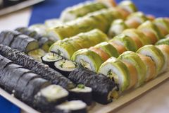 Avocado nori sushi rolls. A variety of avocado and salmon sushi rolls, on a tray stock image