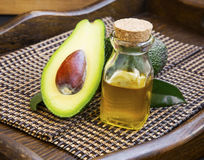 Avocado oil in bottle with avocado fruit Royalty Free Stock Images