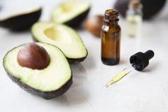 Avocado Oil Dropper Bottle. Small bottle with dropper of avocado oil and avocados on marble surface stock photos