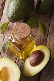 Avocado oil in a glass bottle on a table closeup, vertical top Royalty Free Stock Images