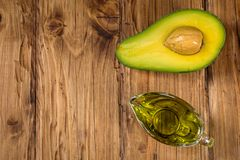 Avocado oil in a glass bowl and fresh organic avocado on old wooden background. Healthy eating, diet, body care concept. Space for royalty free stock photography