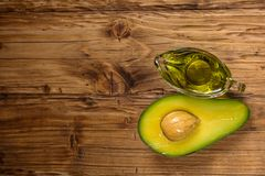 Avocado oil in a glass bowl and fresh organic avocado on old wooden background.Healthy eating,diet,body care concept. Space for stock images