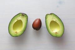 Avocado op een witte houten achtergrond De twee helften van avocado en pit, noot Vegetarisme en gezonde voeding stock foto's