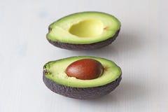 Avocado op een witte houten achtergrond De twee helften van avocado en pit, noot Vegetarisme en gezonde voeding stock afbeelding