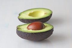 Avocado op een witte houten achtergrond De twee helften van avocado en pit, noot Vegetarisme en gezonde voeding stock fotografie