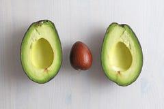 Avocado op een witte houten achtergrond De twee helften van avocado en pit, noot Vegetarisme en gezonde voeding royalty-vrije stock foto