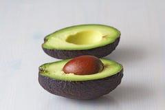 Avocado op een witte houten achtergrond De twee helften van avocado en pit, noot Vegetarisme en gezonde voeding royalty-vrije stock afbeeldingen