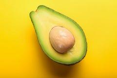 Avocado op gele achtergrond Stock Afbeeldingen