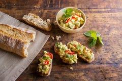 Avocado op plakken van bruschetta tegen houten lijst wordt uitgespreid die royalty-vrije stock afbeelding