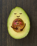 Avocado Parent and Child. A sliced Avocado `parent` holding its round seed `baby` lovingly stock photography