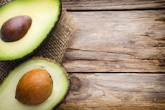 Avocado parts on the wooden table. Royalty Free Stock Images