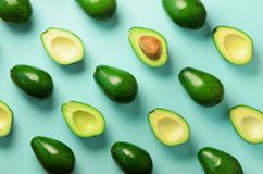 Avocado pattern on blue background. Top view. Banner. Pop art design, creative summer food concept. Green avocadoes, minimal flat. Lay style stock image