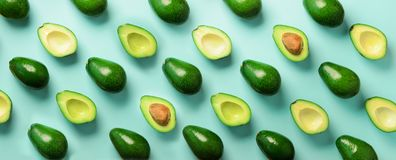 Avocado pattern on blue background. Top view. Banner. Pop art design, creative summer food concept. Green avocadoes, minimal flat. Lay style. Banner royalty free stock photo