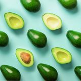 Avocado pattern on blue background. Top view. Banner. Pop art design, creative summer food concept. Green avocadoes, minimal flat. Lay style. Square crop stock photos