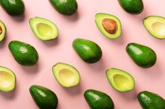 Avocado pattern on pink background. Top view. Banner. Pop art design, creative summer food concept. Green avocadoes, minimal flat. Lay style stock photos