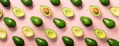 Avocado pattern on pink background. Top view. Banner. Pop art design, creative summer food concept. Green avocadoes, minimal flat. Lay style. Banner royalty free stock photos
