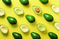 Avocado pattern on yellow background. Top view. Banner. Pop art design, creative summer food concept. Green avocadoes, minimal fla. T lay style royalty free stock image
