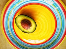 Avocado. A photograph showing a cut half pear of an avocado with seed intact and placed on a bright colorful plate with Mexican ring colors. Healthy food theme stock photos