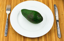 Avocado on a plate with cutlery Royalty Free Stock Photo