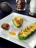 Avocado plate. Slices of avocado with spices on a white plate Royalty Free Stock Photography