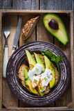 Avocado poached egg toast on plate in vintage wooden tray Stock Photos