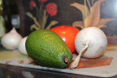 Avocado, pomodoro nella società delle cipolle bianche Immagine Stock