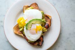 Avocado with pouched eggs and bacon on toast stock photo
