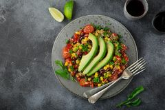 Avocado, quinoa, bean, corn and bell pepper salad, grey background. Top view stock photo