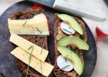 Avocado, radish and cheese on black bread Stock Photos