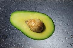 Avocado on red background. Sliced avocado on wet dark background stock photography