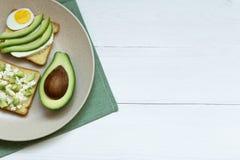 Avocado, ricotta, jajko ?ciska na ceramicznym talerzu nad bia?ym drewnianym t?em, odg?rny widok, kopii przestrze? zdjęcia stock