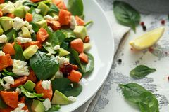 Avocado, roasted sweet potato, spinach, feta cheese healthy salad in white plate. royalty free stock images