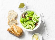 Avocado, romano, kumato tomatoes salad and whole wheat branny bread on light background, top view. Healthy diet vegetarian food. Concept stock images
