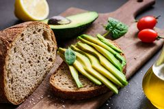 Avocado and rye bread toast on cutting board. Closeup view stock images