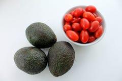Avocado's en kersentomaten op een witte geïsoleerde achtergrond Royalty-vrije Stock Foto's