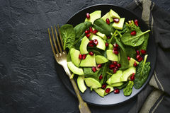 Avocado salad with baby spinach and pomegranate.Top view with co Royalty Free Stock Images