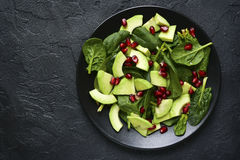 Avocado salad with baby spinach and pomegranate.Top view with co Royalty Free Stock Photos