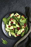 Avocado salad with baby spinach and pomegranate.Top view with co Stock Image