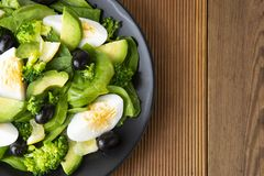 Avocado salad with broccoli, spinach, olives and boiled eggs in black plate, over wooden table. Healthy food. Avocado royalty free stock photography