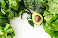 Avocado, salad, broccoli, spinach and pepper on white background. Healthy food concept with fresh assorted green. Avocado, salad, broccoli and pepper on white Stock Images