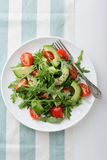 Avocado Salad with cherry tomatoes and arugula on a stripy backg Stock Image
