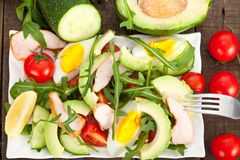 Avocado salad with chicken, rucola and cherry tomatoes in white plate. stock images