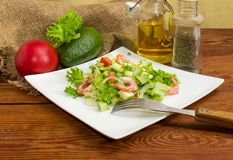 Avocado salad with vegetables and some ingredients for its prepa. Salad made of sliced avocado, vegetables, diced mozzarella cheese and decorated with shrimps royalty free stock photography