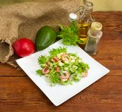 Avocado salad with vegetables and some ingredients for its prepa. Salad made of sliced avocado, vegetables, diced mozzarella cheese and decorated with shrimps stock photography