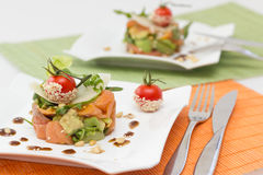 Avocado and salmon salad on square plate. Avocado and salmon salad with tomato  on square plate Royalty Free Stock Photo