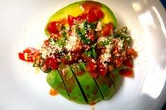 Avocado-Salsa überzogen auf einem weißen Teller lizenzfreie stockfotos