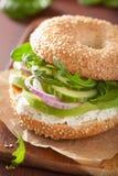 Avocado sandwich on bagel with cream cheese onion cucumber arugula.  royalty free stock photos